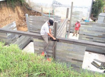 Local labor is trained to build inexpensive housing using leg-like blocks of re-molded plastic waste