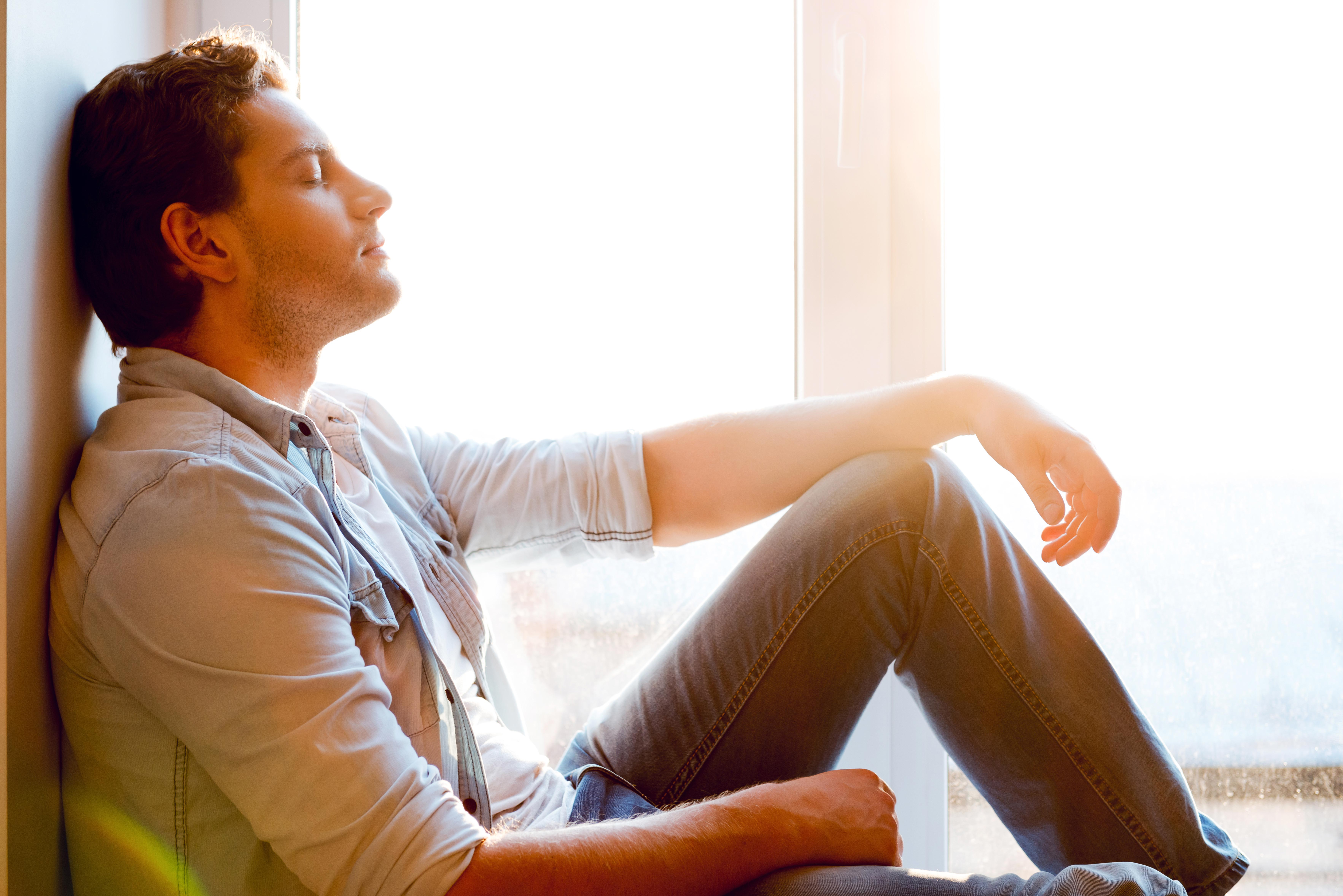 Man enjoying peace and quiet by a window